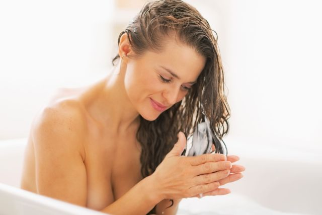 Happy young woman applying hair conditioner in bathtub